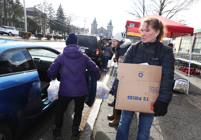 Third Tuesday of the month is food bank day for STEM Academy families. Today's was publicized more widely, and served an estimated 150 families. Lisa Tenczar of Lowell, a teacher at Cardinal Early Learning Center, carries a box of food to a car. (SUN/Julia Malakie)