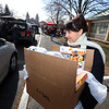 Third Tuesday of the month is food bank day for STEM Academy families. Today's was publicized more widely, and served an estimated 150 families. Cheryl Manucci of Methuen, whose son works for Aramark in Lowell, carries a carton to a car. (SUN/Julia Malakie)