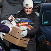 Third Tuesday of the month is food bank day for STEM Academy families. Today's was publicized more widely, and served an estimated 150 families. Maggie Nowak of Cambridge, Lowell Public Schools farm to school manager, brings food to a car. (SUN/Julia Malakie)