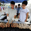 Globe/T. Rob Brown<br /> Khanh Trinh (left), youth leader, and David Pham, 16, both of Fort Smith, Ark., grill pork  balls on sticks Wednesday afternoon, Aug. 7, 2013, at Marian Days in Carthage.