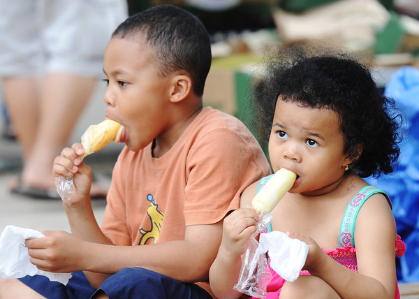 Globe/T. Rob Brown<br /> Siblings 4-year-old Connie Lester (right) and 8-year-old Given Lester, of the state of Minnesota, eat jack fruit ice cream bars on sticks Wednesday afternoon, Aug. 7, 2013, at Marian Days in Carthage.
