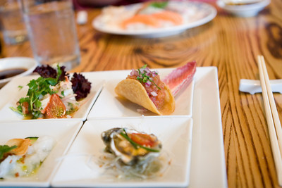 Course #2: a plate of 4 dishes (clockwise from the top left): lobster ceviche, salmon taco, oyster with uni, octopus sashimi.  focus on salmon taco.
