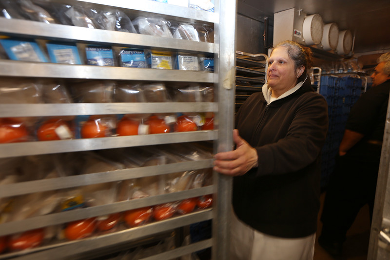 Employees of Lindley Trio Community Meals prepack dinners for Monday distribution by Meals on Wheels organizations, in rented space at Greater Lowell Technical School. They provide about 2,400 hot lunches and 2,400 cold dinners that are distributed in the Merrimack Valley. Nancy DeCunto of Methuen moves a rack of dinners into a walk-in refrigerator. (SUN/Julia Malakie)