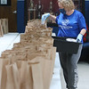 Employees at the Boys & Girls Club of Greater Lowell prepare portions and put together lunch and dinners bags for pickup -- 250 of each daily. Michelle Solazzi of Lowell, whose normal job is lead education in the Brain Center, puts wraps in the lunch bags. (SUN/Julia Malakie)