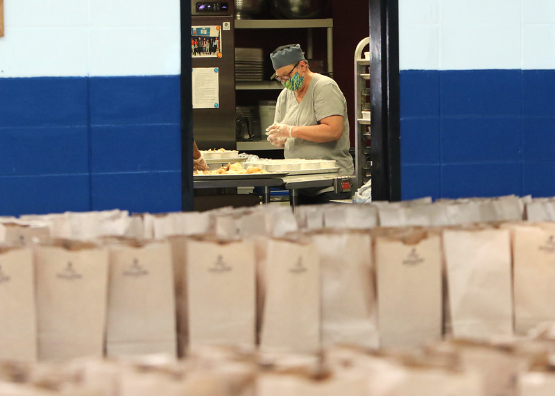 Employees at the Boys & Girls Club of Greater Lowell prepare portions and put together lunch and dinners bags for pickup -- 250 of each daily. Nutrition manager Sally Thayer of Lowell puts lids on containers of baked chicken for the dinner bags. (SUN/Julia Malakie)