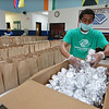 Employees at the Boys & Girls Club of Greater Lowell prepare portions and put together lunch and dinners bags for pickup -- 250 of each daily. Intern Daury Castro of Lowell, Lowell High Class of 2020, puts rolls in dinner bags. (SUN/Julia Malakie)