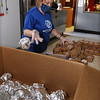 Employees at the Boys & Girls Club of Greater Lowell prepare portions and put together lunch and dinners bags for pickup -- 250 of each daily. Michelle Solazzi of Lowell, whose normal job is lead education in the Brain Center, wraps whole wheat rolls individually. (SUN/Julia Malakie)