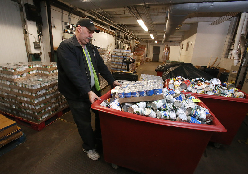 Merrimack Valley Food Bank warehouse assistant and truck driver Tony Agrella of Dracut moves bins of donated food to go upstairs for storage and sorting. (SUN/Julia Malakie)
