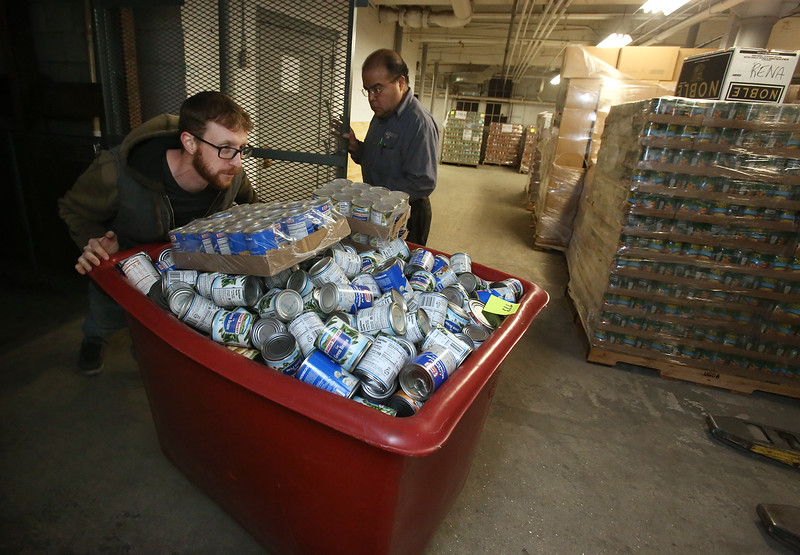 Merrimack Valley Food Bank employees shift bins of donated food upstairs for storage and sorting, and moving USDA and MEFAP pallets downstairs to get ready for Monday customers. Warehouse assistant Brandon Crocker of Pepperell, left, and warehouse manager Tony Luna of Lowell, rear. (SUN/Julia Malakie)