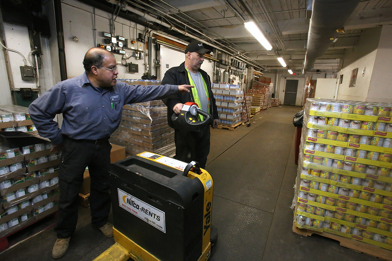 Merrimack Valley Food Bank warehouse manager Tony Luna of Lowell, left, and warehouse assistant and truck driver Tony Agrella of Dracut, right, shift pallets of USDA and MEFAP food contributions downstairs to get ready for Monday customers. (SUN/Julia Malakie)