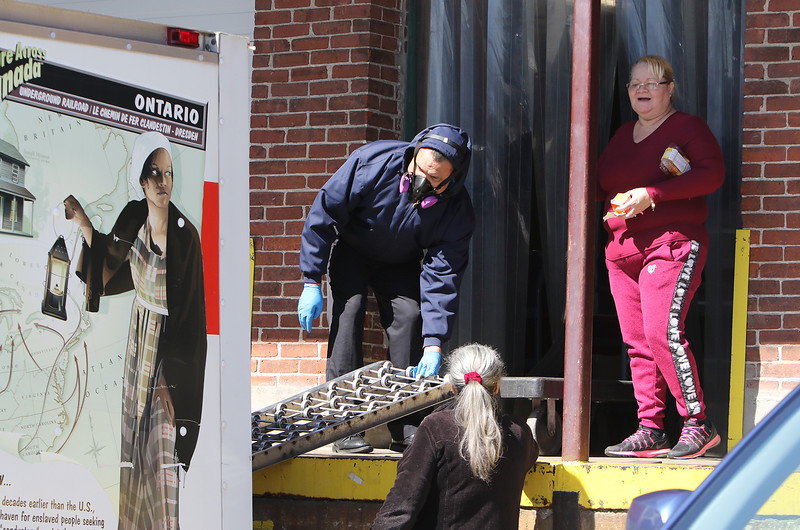 Organizations continue to pick up food for local food pantries from the Merrimack Valley Food Bank. Santiago Ferreira, left, and Wilma Santiago of Lawrence, directo of Water Sources food pantry in Lawrence, finish their weekly pickup of food.  (SUN/Julia Malakie)