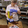 Merrimack Valley Food Bank in Lowell is celebrating its 30th anniversary in 2021. Mitsy Walton, 85, of Dracut, who has been a volunteer at the Food Bank since 2001, checks expiration dates on items from a YMCA food drive collected in Belvidere. JULIA MALAKIE/LOWELLSUN
