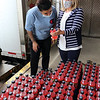 Merrimack Valley Food Bank in Lowell is celebrating its 30th anniversary in 2021. Warehouse worker Kiara Velazquez of Lowell, left, and executive director Amy Pessia look at the ingredients of Mountain Dew. JULIA MALAKIE/LOWELLSUN