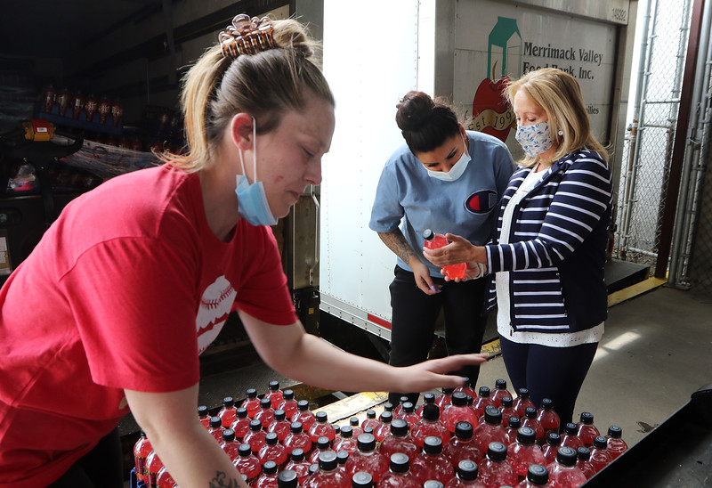 Merrimack Valley Food Bank in Lowell is celebrating its 30th anniversary in 2021. From left, warehouse worker Danielle Landry of Lowell unloads packs of Mountain Dew that needed to be unloaded by hand because they slipped on the pallet jack, as warehouse worker Kiara Velazquez of Lowell and executive director Amy Pessia look at the ingredients. JULIA MALAKIE/LOWELLSUN