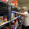 Merrimack Valley Food Bank in Lowell is celebrating its 30th anniversary in 2021. Mitsy Walton, 85, of Dracut, who has been a volunteer at the Food Bank since 2001, shelves items from a YMCA food drive collected in Belvidere. JULIA MALAKIE/LOWELLSUN