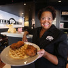 Mill City BBQ at its new location at 11 Kearney Square in Lowell. Owner Renay Wolterding with a serving of Chicken & Waffles. (SUN/Julia Malakie)
