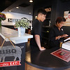 Mill City BBQ at its new location at 11 Kearney Square in Lowell. Owner Renay Wolterding, right, with waiter Phoenix Sun of Lowell, taking a catering order. (SUN/Julia Malakie)