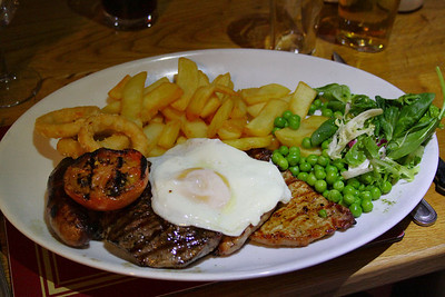 Mixed grill - Rump steak, gammon steak, pork steak, butchers sausage, fried egg, fries, onion rings, grilled tomato, garden peas and dressed leaves. £14.50 Served in The Allerford Inn near Taunton  12/04/12