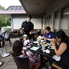 Moonstones restaurant in Chelmsford is open for outdoor dining as part of phase 2 of reopening the economy during the COVID-19 pandemic.  Server Kraig Scharn of Chelmsford pours water for Tomoko and husband Shawn Patterson of Chelmsford, eating with daughters Mae, 5, rear, and Hannah, 7. (SUN/Julia Malakie)