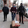 Lowell Democratic City Committee chair Judith Durant, left, and Ward 2 chair Sally Coulter, right, both of Lowell, walk with Open Pantry executive director Geoff Bryant as he moves the last of about 500 lbs of food donated on behalf of the Lowell Democratic City Committee, along with monetary contributions.  (SUN/Julia Malakie)