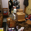 Tom Buretta of Chelmsford, president of the board, and a volunteer at the Open Pantry of Greater Lowell, stacks the last of about 500 lbs of food donated by the Lowell Democratic City Committee.  (SUN/Julia Malakie)