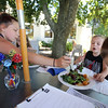 Outdoor dining at the Gallery Cafe at 529 King Street in Littleton. From left, Chloe Greenslade, 12, and her cousins, siblings Jaden Greenslade, 10, hidden, Kenny, 9, eating the House Special Salad, and Mason, 4, photobombing. (SUN/Julia Malakie)