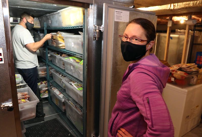 Volunteers put away donated food at the PACH Outreach food pantry in Pepperell. Jennie Jussaume, right, waits while Cory Dows rearranges bins in a very full freezer. Both are from Pepperell. JULIA MALAKIE/LOWELLSUN