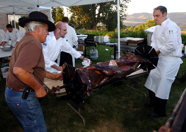 Chefs Yvon Gros, left, Michael Scott, and Adam Dulye, take the cooked lambs out of the roaster.<br /> Students from the Culinary School of the Rockies spend 10 days in Paonia, Colo. and the surrounding area learning where food comes from.<br /> <br /> <br /> Cliff Grassmick/ September 16, 2008