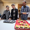 """Lawrence Library in Pepperell holds its fifth annual Cupcake Festival fundraiser. From left, Eric Griffith, 10, his brother Nathan, 14, and their father Ben Griffith of Pepperell, debate what to pick for their last of six cupcakes. Eric's entry in the contest was the """"cupcake sliders"""" in front. (SUN/Julia Malakie)"""