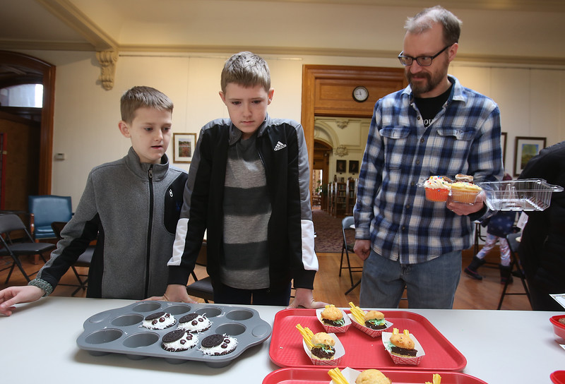 """Lawrence Library in Pepperell holds its fifth annual Cupcake Festival fundraiser. From left, Eric Griffith, 10, his brother Nathan, 14, and their father Ben Griffith of Pepperell, debate what to pick for their last of six cupcakes. Eric's entry in the contest was the """"cupcake sliders"""" at right. (SUN/Julia Malakie)"""