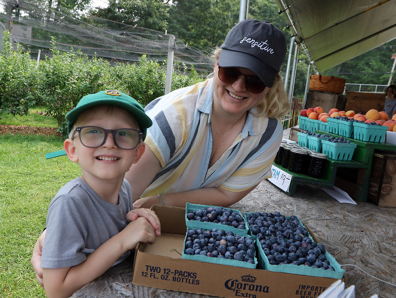 JUly 20, 2021 -- Pick your own blueberries is underway at Doe Orchards in Harvard, and is expected to run through mid-August. Teddy Light, 4, and his mother Amanda Light, of Littleton, are happy with their haul. Doe Orchards also has a huge peach crop this year, thanks to not too much heat or frost in February, and peaches are available, but pick your own peaches will not start unitl around mid-August. SUN/Julia Malakie