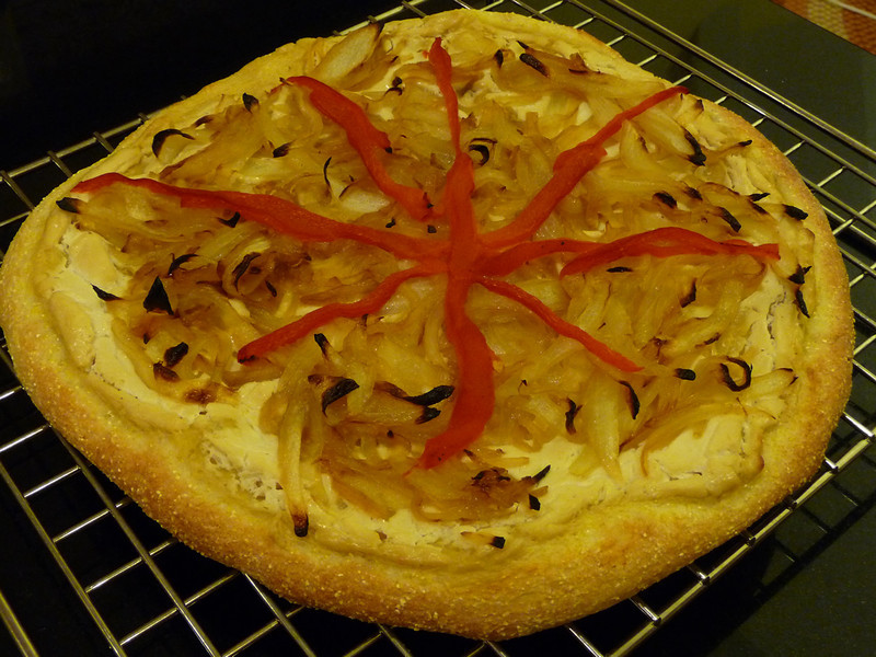 """<h1>White Pizza</h1> This is an adaptation of a recipe from Nava Atlas in her fabulous cookbook called <i><b>Vegan Express</b></i>.  Roast about 8 cloves of garlic (place 8 cloves, drizzled with a touch of olive oil in a little piece of aluminum foil ... don't wrap them up or anything ... the foil just acts as a holder for the garlic and oil).  Roast at 425°F for 15 minutes or so ... until slightly browned, but not burned.   It works well to do this when you're using the oven for something else.  In a food processor, puree up one box of firm or extra firm silken tofu (12.3 ounces).   Add in the 8 cloves of roasted garlic and 1 teaspoon salt.   Puree till smooth.  Spread this garlic-y spread on a pizza crust.  Top with caramelized onions.  Add some roasted red pepper strips for color.    Bake at 425° till crust is done and all toppings are hot.  For gluten free folks, <a href=""""http://www.amazon.com/Namaste-Foods-Gluten-Pizza-16-Ounce/dp/B000LKZA1I"""" rel=""""nofollow"""">this pizza crust mix</a>, while a bit pricey, is SUPER tasty!"""