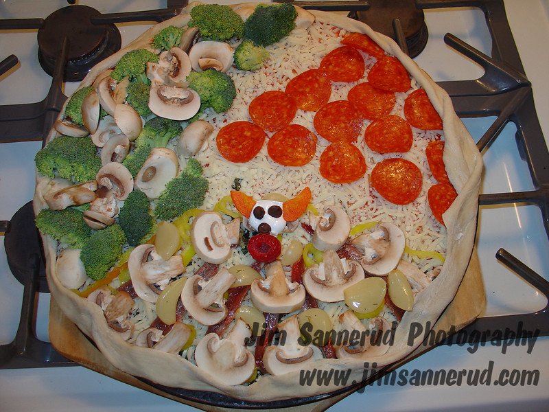 "Jim's homemade pizza. My sons always like the same thing on their third: one only likes pepperoni, and the other only wants mushrooms and broccoli. Boring. I get creative on my third. I usually start with anchovies and mushrooms. This one also has fresh garlic cloves. I usually finish with something bizarre to horrify my kids. In this case it is a little clown face made from a marshmallow, with chocolate chips for eyes and nose, carrots for Bozo hair, and a raspberry for the mouth. This is before cooking. Bozo melted a bit from cooking, but he is still recognizable in the ""after"" picture in my gallery."
