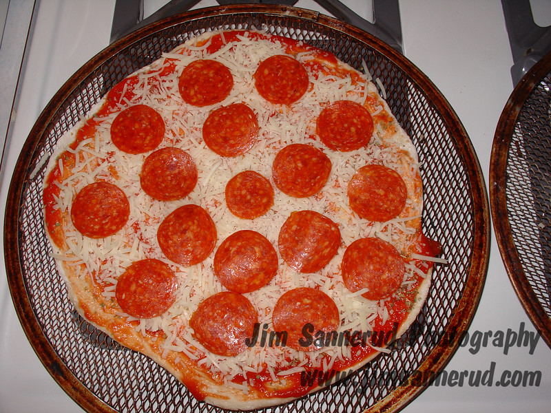 """Jim's homemade pizza. Usually we make one large 14"""" pie divided in thirds, but sometimes we use a double batch of dough and make three individual 10"""" mini-pizzas. This one is pepperoni, my youngest son's favorite and his standard order, before cooking. You can see the """"after"""" picture right out of the oven in my gallery."""