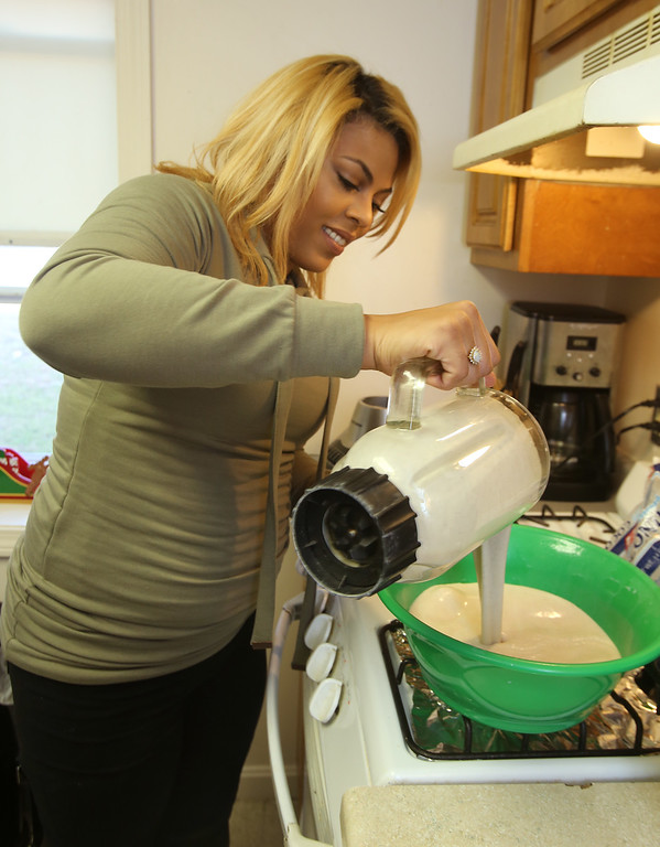 . Xiomara Santos of Lowell makes coquito, a popular coconut-based holiday drink among Puerto Ricans, similar to eggnog. Her ingredients are coconut milk, evaporated milk, sweetened condensed milk, cinnamon, coconut flakes, and vanilla, and two ingredients she keeps secret to keep her recipe special. (SUN/Julia Malakie)