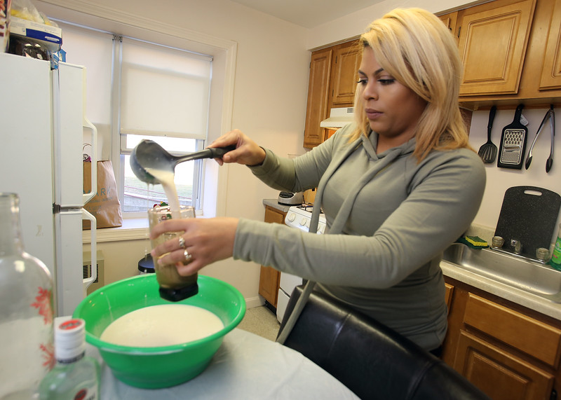Xiomara Santos of Lowell pours a glass of coquito she'd just mixed, a popular coconut-based holiday drink among Puerto Ricans, similar to eggnog. Her ingredients are coconut milk, evaporated milk, sweetened condensed milk, cinnamon, coconut flakes, and vanilla, and two ingredients she keeps secret to keep her recipe special. (SUN/Julia Malakie)