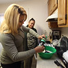 Xiomara Santos of Lowell makes coquito, a popular coconut-based holiday drink among Puerto Ricans, similar to eggnog. Her friend Thalia Lopez of Lowell, rear, was looking forward to drinking it. (SUN/Julia Malakie)