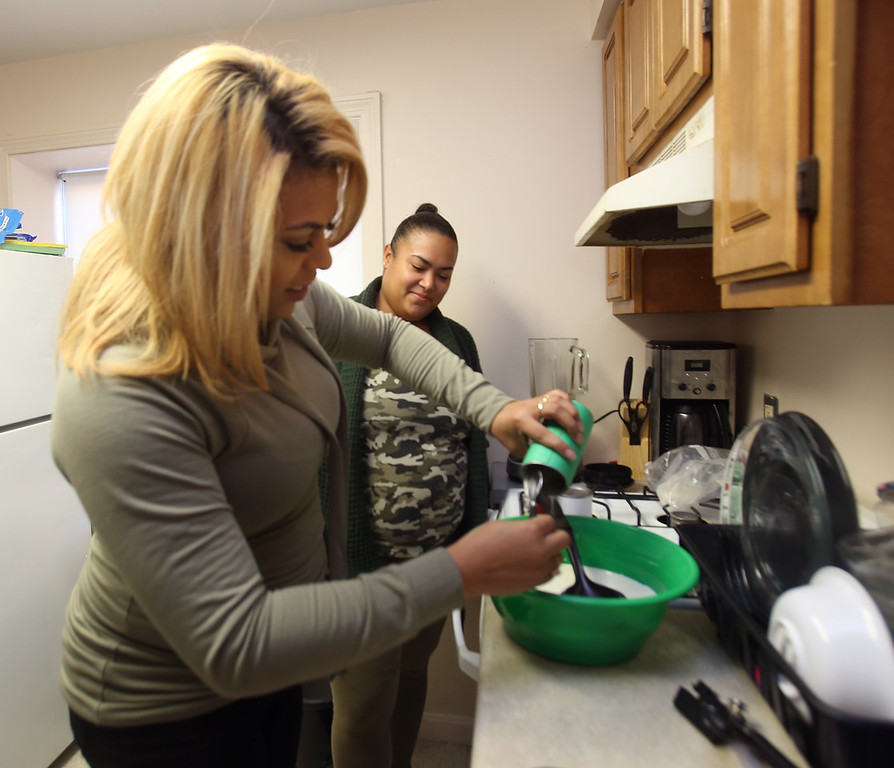 . Xiomara Santos of Lowell makes coquito, a popular coconut-based holiday drink among Puerto Ricans, similar to eggnog. Her friend Thalia Lopez of Lowell, rear, was looking forward to drinking it. (SUN/Julia Malakie)