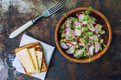 Salad with radishes, apples, greens and a sandwich  fish pate. Old background