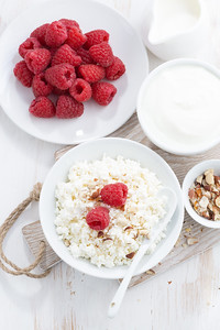 homemade cottage cheese with raspberry, milk and yogurt on white table