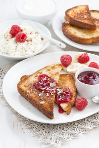 sweet breakfast - crispy toasts with raspberries, banana and jam, vertical