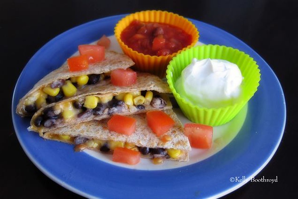 Black Beans & Corn Quesadillas<br />  This one was very easy, great week night meal and the kids loved it. This recipe is from the Hy-Vee Magazine.<br />  1 (15 ounce) can reduced fat-sodium black beans, drained and rinsed<br />  1 cup frozen corn, thawed ( I used canned instead)<br />  2/3 cup finely shredded mexican blend cheese<br />  4 multigrain tortillas<br />  2 tsp olive oil<br />  1 chopped tomato (optional)<br />  Salsa of your choice<br />  sour cream (optional)<br /> <br />  In a medium bowl, stir together beans, corn and cheese. Spread about 3/4 cup of mixture on half of each tortilla. Fold in half, pressing gently to flatten. In a large nonstick skillel, heat 1 tsp olive oil over medium heat. Place 2 quesadillas in hot skillet, cook 1-2 minutes per side or until golden. Transfer to cutting board. Repeat with remaining quesadillas. Cut into wedges and serve with desired garnishes.