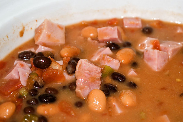 """<font size=""""3"""">Spicy Bean Soup<br></font><font size=""""2""""> This is a high fiber, low-fat soup that's full of flavor.  The soup in the photo is a variation with diced ham.  Here's the basic version:<br></font><font size=""""1"""">  One 14.5 oz. can low fat chicken broth One 14.5 oz. can fat-free refried beans One 14.5 oz. can black beans One 14.5 oz. can pinto beans One 10 oz. can Rotel brand diced tomatos and green chilis <br></font><font size=""""2""""> This can't be easier.  Open the cans, drain and rinse the beans, pour everything into a pan.  Bring to a boil, then reduce the heat and simmer for about 20 minutes.  This also can be made in a crock pot.<br><br>Variations: Add diced ham. Sub vegetable broth for the chicken broth. Sub the diced tamatos with the spicy version.  </font>"""