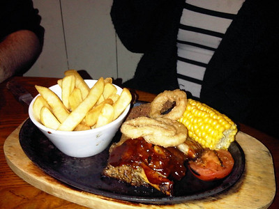 "All American Combo - Half rack of BBQ glazed pork ribs, Southern Fried chicken fillets, corn on the cob and onion rings. Served with seasoned chips and half a grilled tomato. £7.19.  Served in ""Sizzling Pubs""  12/10/12"