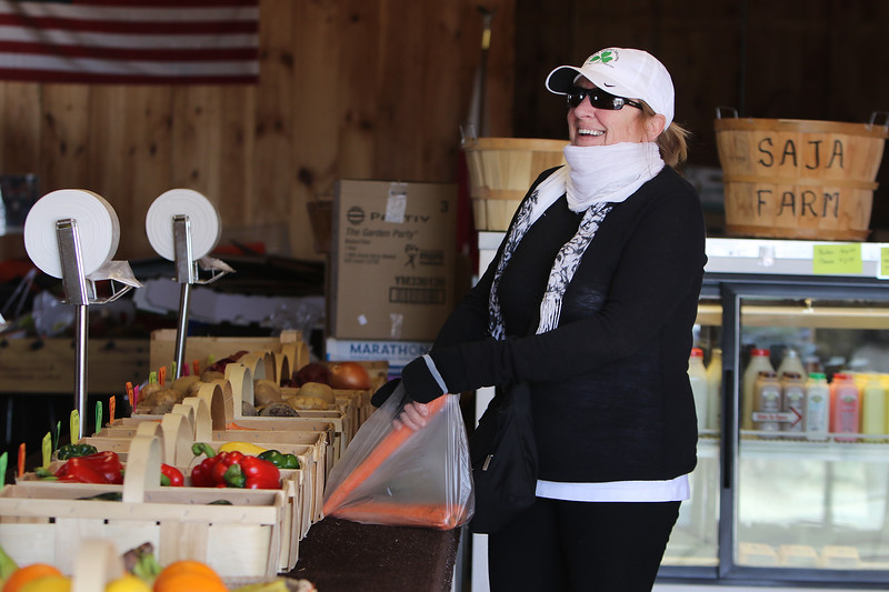 Peg Biedron of Dracut buys vegetables at Saja Farm, where owner Caroline Zuk of Dracut has opened the farmstand early in the season, with produce brought from Boston, to help local residents during the Covid-19 emergency. She was delighted to find carrots. (SUN/Julia Malakie)
