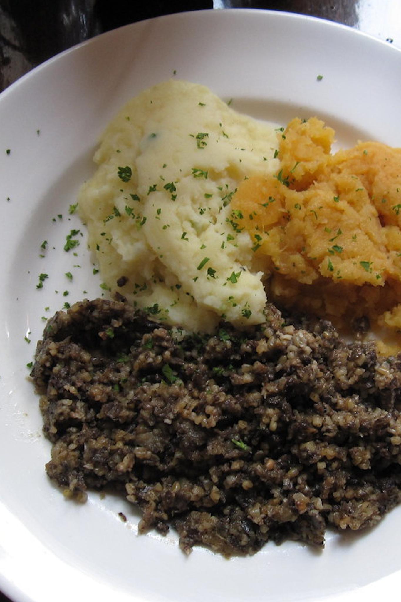 Scottish foods haggis, potatoes and turnip on a plate.