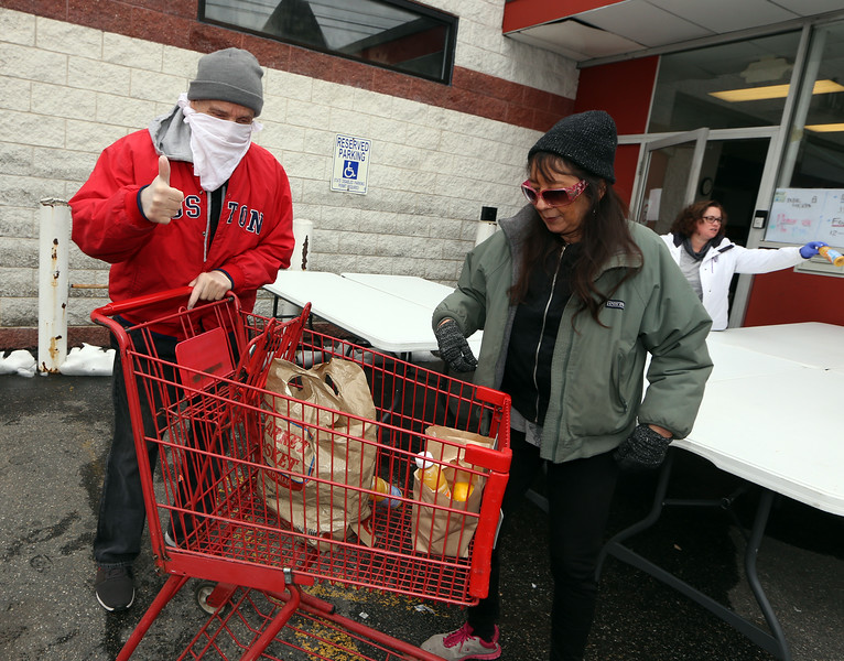 Life Connection Center on Appleton Street is giving out lunch M-W this week, and M-F starting next week, as a result of the coronavirus emergency. Laura Miragliotta, right, who lives in nearby public housing, and her boyfriend John Ferrari of Billerica, get lunch. (SUN/Julia Malakie)