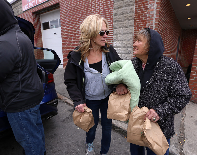 Volunteers with Under the Oak at Christ Church United, and Living Waters, hand out lunch including sandwiches and coffee on South Street to homeless and people in need. Volunteer Annette Martell of Billerica, left, who helps run Under the Oak, talks with Penny Cote of Lowell, who took a blanket because she's been sleeping outside, and lunches for a couple of men across the street. (SUN/Julia Malakie)