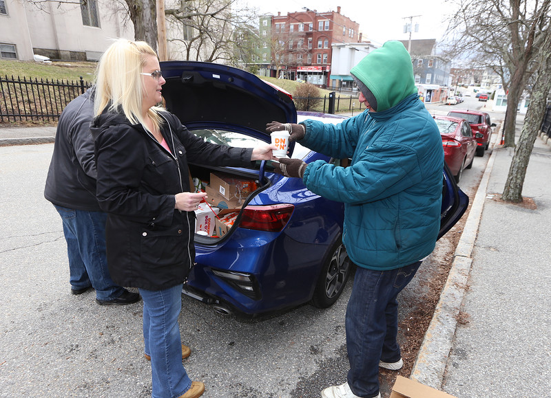 Volunteers with Under the Oak at Christ Church United, and Living Waters, hand out lunch including sandwiches and coffee to homeless and people in need. Volunteer Raegan Downs of Lowell, left, hands coffee to a guest outside the church.  (SUN/Julia Malakie)