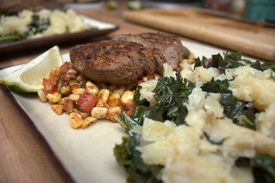 steak over corn salad with colcannon